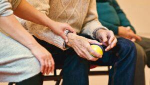 Senior knetet Ball in der Hand zur Kontrakturenprophylaxe. Eine Übung, um Kontrakturen vorzubeugen.